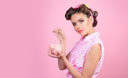 Pin up woman with trendy makeup. pinup girl with fashion hair. retro woman with moneybox. loan. Money. Housewife. pretty. Girl in vintage style, copy space. You stock image