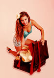 Pin up woman tries to close suitcase, in retro Stock Photo