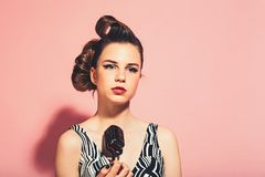 Pin up young girl on pink background, radio. royalty free stock photo