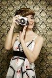 Pin upp flicka med den retro kameran fotografering för bildbyråer