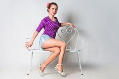 Pin vers le haut de la fille s'asseyant sur le banc et le regard Photo stock