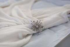Pin on white dress. Closeup of a decorative pin on a white dress Royalty Free Stock Photography