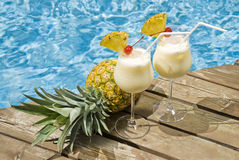 Pina Colada. Two glasses of pina colada and a pineapple by the pool stock images