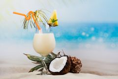 Pina colada cocktail on beach coast. With pineapple and coconut under palm tree. Copy space Stock Photography