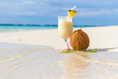 Pina Colada cocktail on the beach. With coconut and exotic flower Stock Images