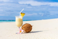 Pina Colada cocktail on the beach. With coconut and exotic flower Stock Image