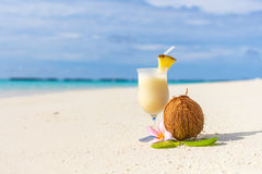 Pina Colada cocktail on the beach. With coconut and exotic flower Stock Photo