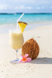 Pina Colada cocktail on the beach. With coconut and exotic flower Royalty Free Stock Photos