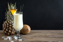 Pina Colada Cocktail. With pineapple and coconut over wooden background, copy space. Summer tropical delicious cocktail royalty free stock image