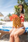 Pina Colada cocktail in pineapple in a female hand. The girl is blurred in the background.  stock photos