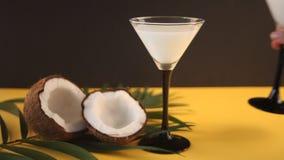 Pina Colada Cocktail, zoete cocktail maakte met rum, kokosnotenroom of kokosmelk op gele lijst en zwarte achtergrond De hand van  stock footage