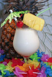 Pina colada - colorful. A pina colada with umbrella, cherry, pineapple slice, straw, and a real uncut pineapple behind the drink Stock Photo
