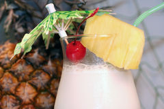 Pina colada - colorful - closeup. A pina colada with umbrella, cherry, pineapple slice, straw, and a real uncut pineapple behind the drink. Closeup of top part Stock Photos