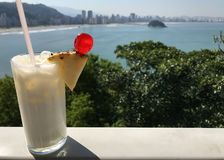 Pina Colada Drink Sits On Ledge Overlooking Spectacular Brazilia royaltyfri fotografi