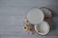 Pina-colada Getränk im Cocktailglas, das mit Kokosnuss und Orchidee verziert wird, blüht Lizenzfreie Stockfotografie