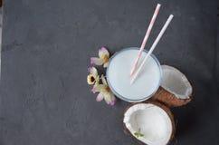 Pina-colada Getränk im Cocktailglas, das mit Kokosnuss und Orchidee verziert wird, blüht Stockbilder