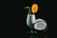 Pina Colada over black background, garnished with  coconut. Royalty Free Stock Images