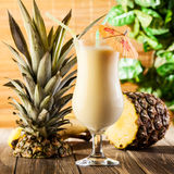 Pina Colada on wooden background garnished pineapple Stock Images