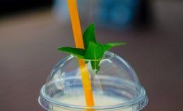 Pina coladacoctail i plactic exponeringsglas med räkningen och tubulen Mintkaramellblad på räkningen arkivbilder