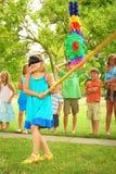 Pinata. Young girl at an outdoor party hitting a pinata Royalty Free Stock Image