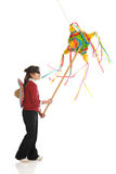 Pinata Girl. A blindfolded girl whacking at a traditional pinata.  Some motion blur on pinata.  Isolated on white Royalty Free Stock Photography