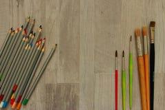 Pincéis de tamanhos diferentes e lápis coloridos no fundo de madeira cinzento como o conceito do desenho Fotografia de Stock Royalty Free