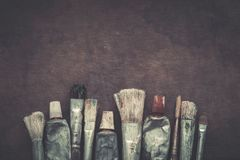 Pincéis do artista, close up dos tubos da pintura no fundo escuro da lona Fotografia de Stock