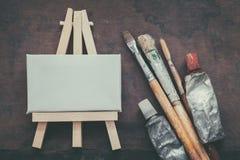 Pincéis do artista, tubos da pintura e armação pequena com close up da lona Vista superior Fotos de Stock