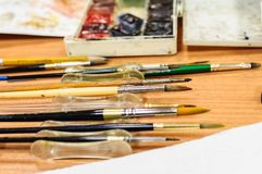 Pincéis e aquarelas na tabela de madeira imagens de stock