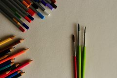 Pincéis finos vermelhos e verdes e lápis coloridos no fundo do Livro Branco como o conceito do desenho Fotos de Stock Royalty Free