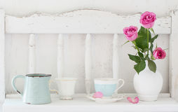 Pinc roses in vase and dinnerware on wooden shelf Royalty Free Stock Image