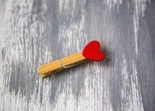 Pince à linge en bois avec le coeur rouge sur le fond peint en bois Photo libre de droits