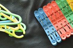 Pince à linge et faim en plastique colorée sur le tissu noir Photo libre de droits