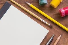 Pinceau, aquarelle, crayon, stylo avec le carnet sur la table en bois, concept créatif Images libres de droits