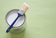 Pinceau et bidon de peinture sur le fond vert Images stock