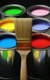 Pinceau et peinture, bidons de peintures colorées primaires sur le Ba noir Photographie stock libre de droits