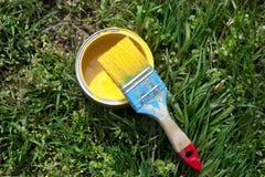 Pinceau et une banque avec la peinture jaune sur l'herbe Image stock