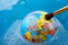 Pinceau placé sur le dessus du globe Photos libres de droits