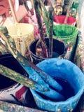 Pinceau utilisé avec différents pots de couleur Photo stock
