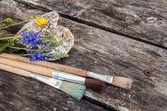 Pinceaux avec les fleurs sauvages et coeur d'écorce sur le vieux boa en bois photos stock