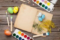 Pinceaux colorés d'oeufs de pâques, de livre et Photo libre de droits