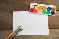 Pinceaux colorés de palette et papier blanc sur la surface en bois Images stock