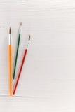 Pinceaux colorés sur le bois blanc texturisé Image libre de droits