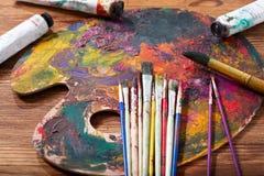 Pinceaux colorés sur une palette Images stock