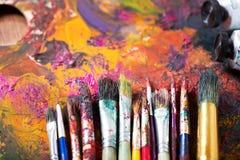 Pinceaux colorés sur une palette Images libres de droits