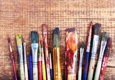 Pinceaux colorés sur une table en bois Photos libres de droits