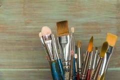 Pinceaux d'artiste au-dessus de texture en bois rustique Image stock