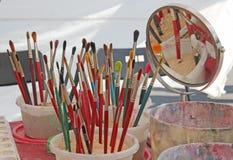 Pinceaux des peintures et des cuvettes de l'eau utilisées pour la peinture de visage Photo stock