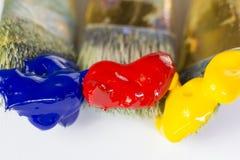Pinceaux du macro trois avec la peinture rouge, jaune et bleue sur un fond blanc Endroit pour le texte, pour la bannière, pour le Photographie stock