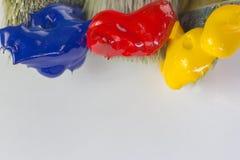 Pinceaux du macro trois avec la peinture rouge, jaune et bleue sur un fond blanc Endroit pour le texte, pour la bannière, pour le Image stock